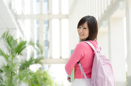 campus building: Young Asian teen student standing outside school campus building, holding file folder and smiling.