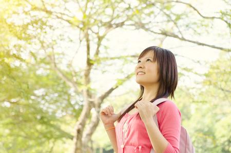 persona pensando: Asia chica estudiante de universidad joven que se coloca en césped del campus, con mochila mirando a otro lado y sonriendo.
