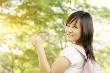 adult education: Young Asian college girl student standing on campus lawn, showing thumb up and smiling.