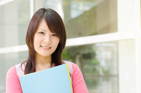campus building: Young Asian adult student standing outside campus building, holding file folder and smiling.