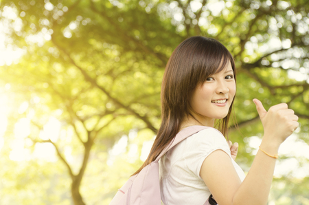 education success: Young Asian university girl student standing on campus lawn, giving thumb up and smiling.