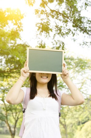 covering face: Young Asian college girl student standing on campus lawn, hands holding a blank chalkboard covering face and smiling.