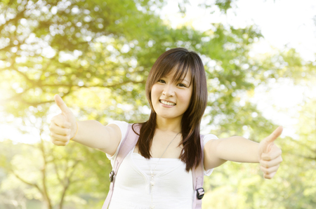 university education: Young Asian college girl student standing on campus lawn, showing thumbs up and smiling.