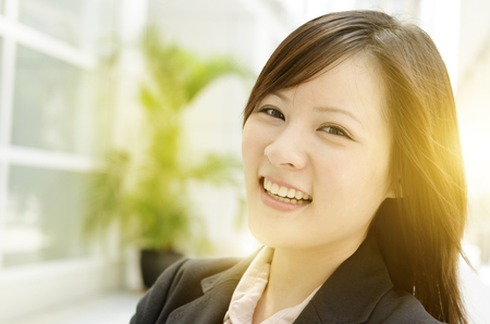 office environment: Portrait of a happy Asian business woman smiling and standing at an office environment, beautiful golden sunlight at background.