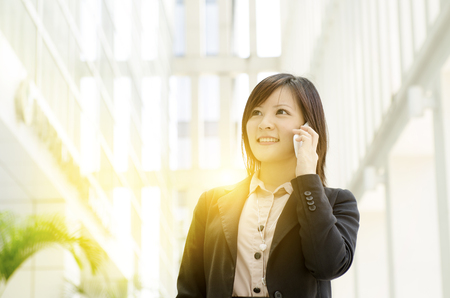 Portrait of a young Asian business woman smiling and talking on smart phone, walking at an office environment, beautiful golden sunlight at background.