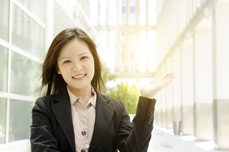 uni: Young Asian business woman hand showing somethings, at an office environment, natural golden sunlight at background. Stock Photo