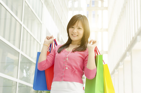 1 person: Happiness, consumerism, sale and people concept. Young Asian girl with shopping bags over mall background. Beautiful golden sunlight at back.