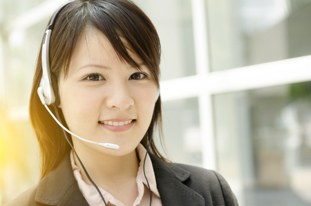 office environment: Portrait of a young Asian female receptionist with headset smiling, at an office environment, natural golden sunlight at background.