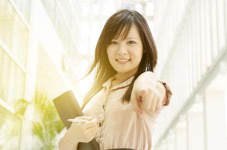 Mujer de negocios asiática joven sonriendo y apuntando a que, de pie en un entorno de oficina, luz natural, sol de oro en el fondo.