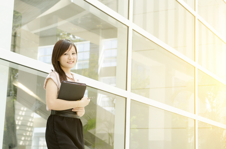 young executive: Young Asian woman executive smiling and standing at an office environment, beautiful golden sunlight at background.
