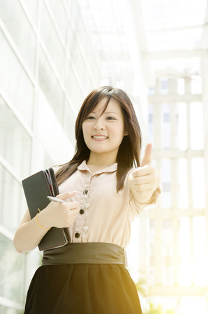 business asia: Young Asian business woman smiling and thumb up at an office environment, beautiful golden sunlight at background.
