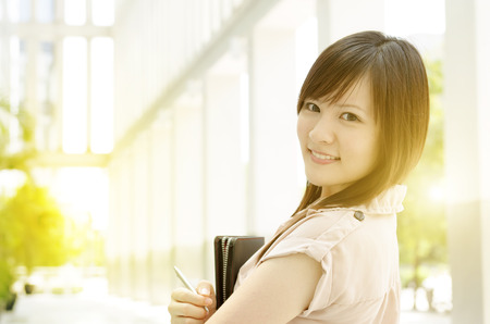 office environment: Young Asian female business people smiling and holding file folder, standing in an office environment, beautiful golden sunlight at background.