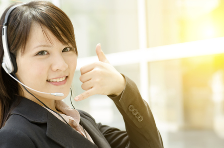 office environment: Portrait of a young Asian customer support with headset smiling, at an office environment, natural golden sunlight at background.