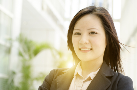 uni: Portrait of a young Asian business woman smiling and standing at an office environment, natural golden sunlight at background.