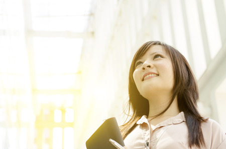 office environment: Young Asian business woman smiling and looking up, standing in an office environment, beautiful golden sunlight at background.
