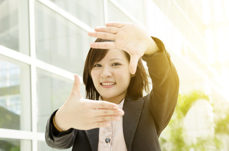 Smiling young Asian business woman making a frame with fingers, at an office environment, natural golden sunlight at background. photo