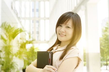 Young Asian female executive smiling and holding file folder, standing in an office environment, beautiful golden sunlight at background. photo
