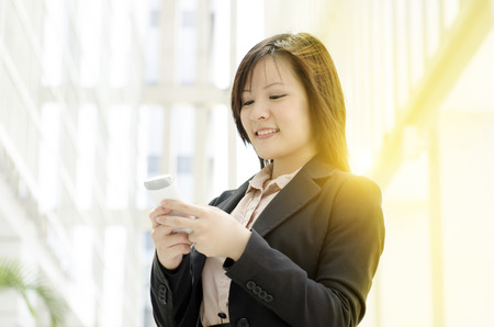 Portrait of a young Asian business woman using smartphone, standing at an office environment, beautiful golden sunlight at background. photo