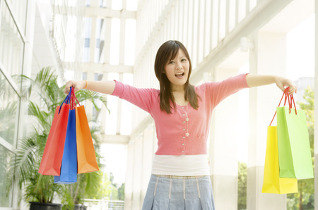 Cheerful young Asian woman with shopping bags walking out the mall. Beautiful golden sunlight at background. photo