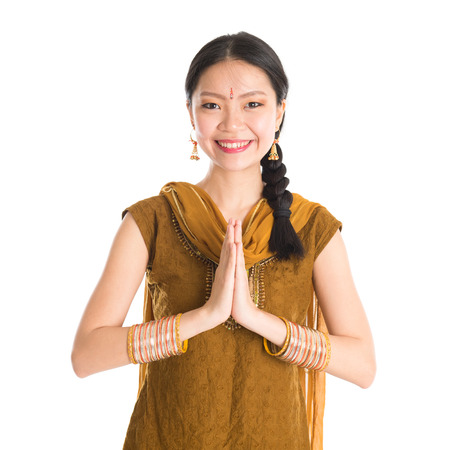 gesturing: Young mixed race Indian Chinese girl in traditional punjabi dress showing greeting gesture, standing isolated on white background. Stock Photo