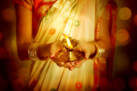Close up Indian woman in traditional sari lighting oil lamp and celebrating Diwali or deepavali, fesitval of lights at temple. Female hands holding oil lamp.