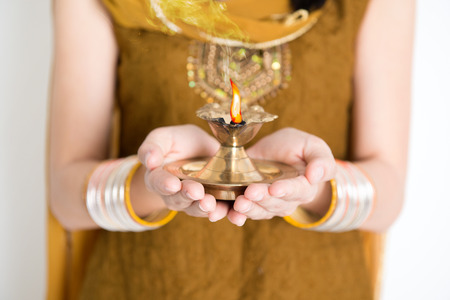 diyas: Close up fair Indian woman in traditional dress hands holding diya oil lamp and celebrating Diwali or deepavali, fesitval of lights. Stock Photo