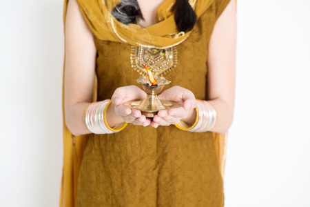 diyas: Fair Indian woman in traditional dress hands holding diya oil lamp and celebrating Diwali or deepavali, fesitval of lights.