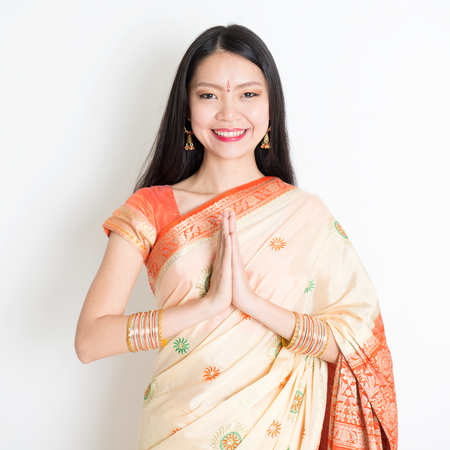 Portrait of mixed race Indian Chinese girl with traditional sari dress in greeting gesture, standing on plain background.