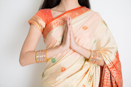 Fair skin Indian woman in traditional sari dress showing welcoming gesture, standing on plain background.