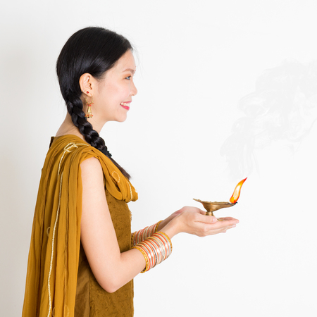 Side view young mixed race Indian Chinese woman in traditional dress hands holding diya oil lamp and celebrating Diwali or deepavali, fesitval of lights.