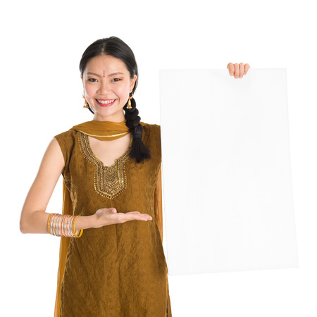 indian fair: Portrait of young mixed race Indian Chinese girl in traditional punjabi dress holding a blank white placard, standing isolated on white background. Stock Photo