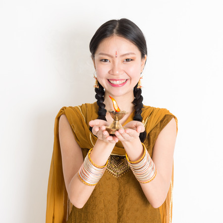 Mixed race Indian Chinese female in traditional dress hands holding diya oil lamp and celebrating Diwali or deepavali, fesitval of lights. Stock Photo