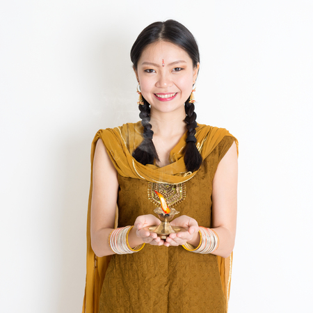 Mixed race Indian Chinese woman in traditional dress hands holding diya oil lamp and celebrating Diwali or deepavali, fesitval of lights.