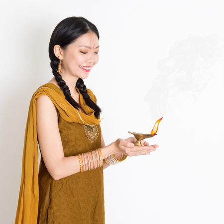 Young mixed race Indian Chinese female in traditional dress hands holding diya oil lamp and celebrating Diwali or deepavali, fesitval of lights. Stock Photo