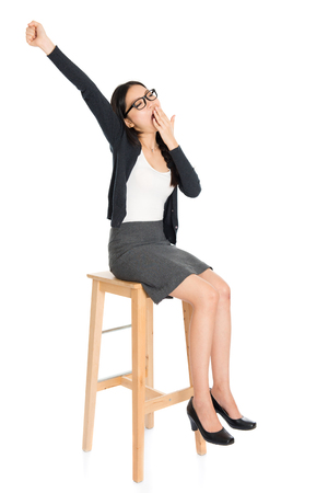 high chair: Full body portrait of young Asian woman yawning, sitting on high chair, isolated on white background.
