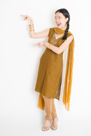 Portrait of young mixed race Indian Chinese girl in traditional punjabi dress fingers pointing at copy space, full length standing on plain white background.
