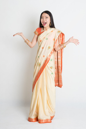 indian fair: Portrait of surprised young mixed race Indian Chinese female in traditional sari dress, full length on plain background.