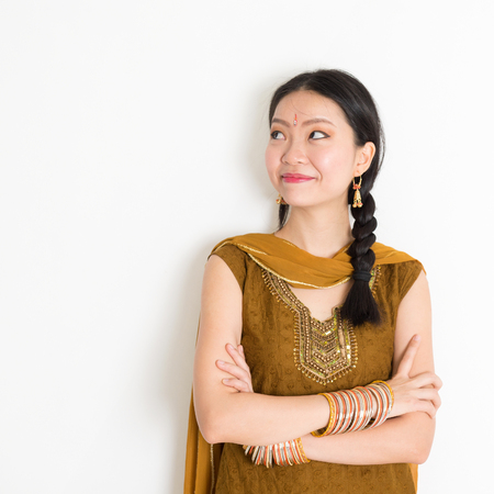 looking at side: Portrait of arms crossed mixed race Indian Chinese girl in traditional Punjabi dress looking side upward, standing on plain white background.