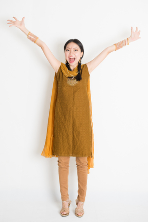 asia women: Portrait of excited mixed race Indian Chinese woman in traditional punjabi dress arms outstretched, full length standing on plain white background.