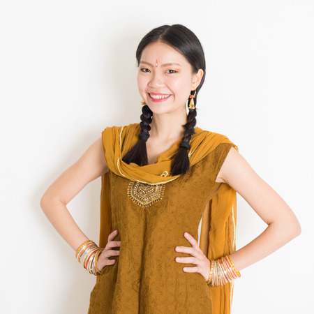 religious clothing: Portrait of beautiful mixed race Indian Chinese girl in traditional Punjabi dress smiling, standing on plain white background.