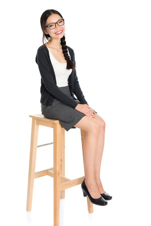 high chair: Full body portrait of young Asian woman sitting on high chair, isolated on white background. Stock Photo
