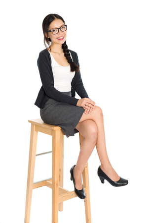 asian businesswoman: Full body portrait of young Asian woman leg crossed sitting on high chair, isolated on white background. Stock Photo