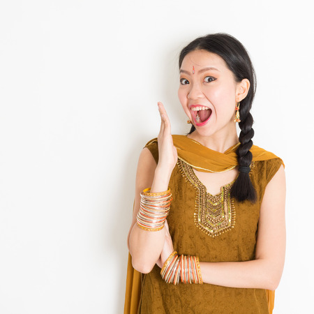 Portrait of shocked mixed race Indian Chinese girl in traditional punjabi dress opened mouth wide, surprised emotion, standing on plain white background.