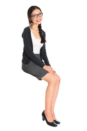 Full body portrait de jeune femme asiatique assis sur une chaise invisible, isolé sur fond blanc.