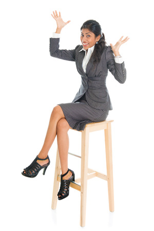 high chair: Happy full body black businesswoman sitting on high chair and hands raised,  isolated on white background. Stock Photo