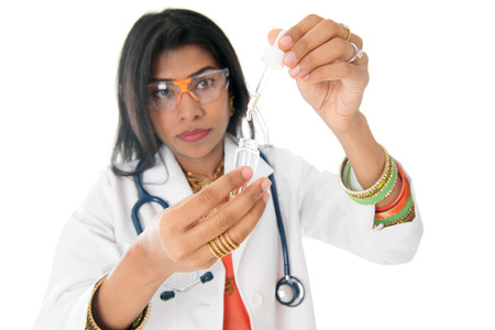 An Indian female medical doctor looking at a test liquid in a laboratory.