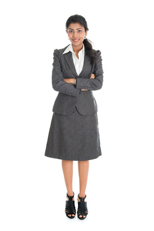 Full length portrait of Indian businesswoman standing arms crossed isolated on white background.