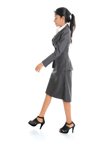 Full length side view of Indian businesswoman walking isolated on white background. Stock Photo