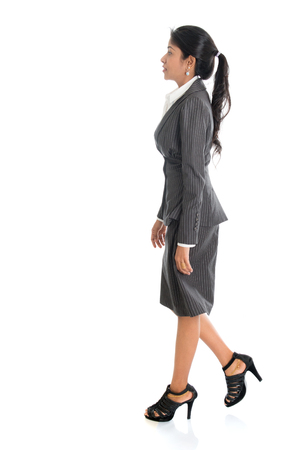 one person: Full length side view of African American businesswoman walking isolated on white background.
