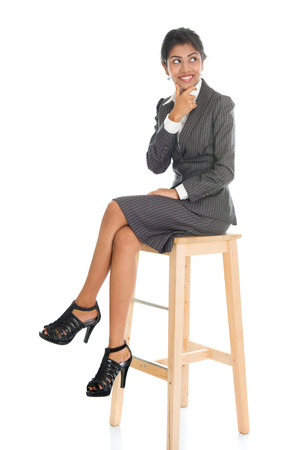 girl legs: Full length black businesswoman sitting on high chair and having a thought, isolated on white background.